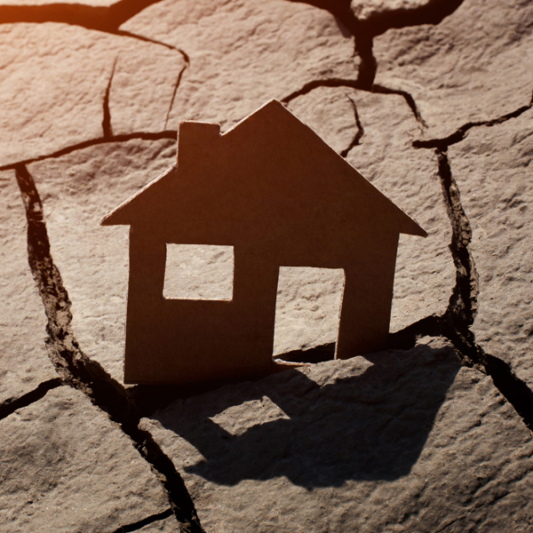 Image of a house sitting on a cracked earthquake fault line.